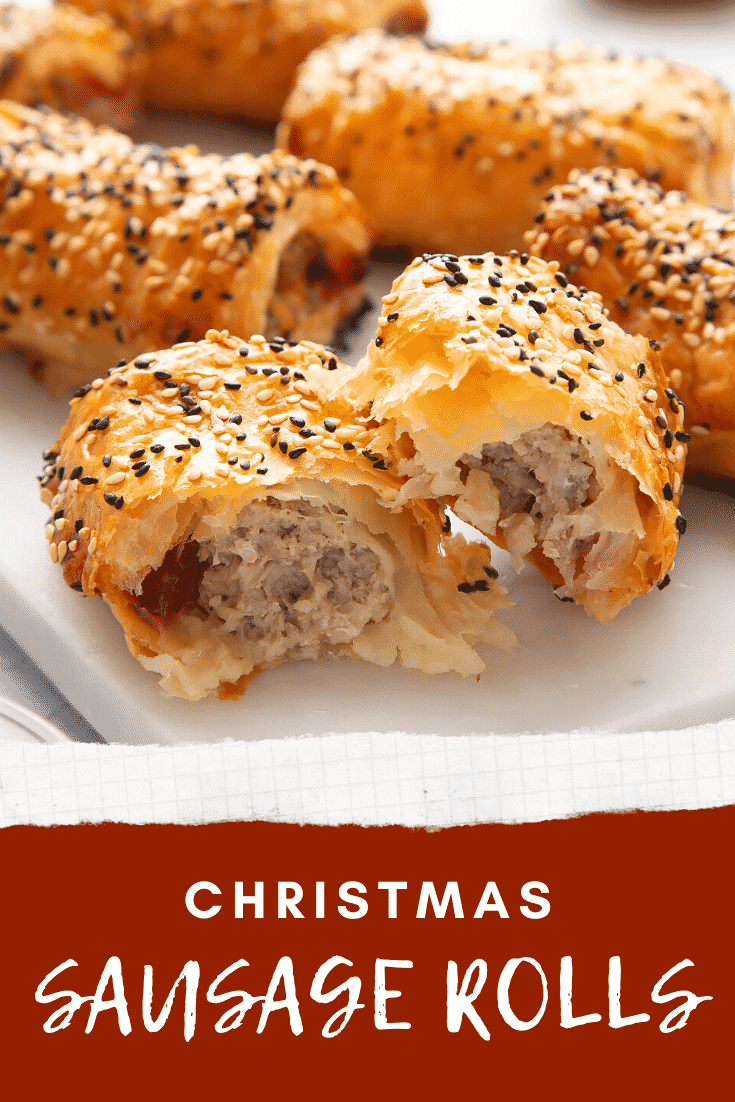 A festive sausage roll broken open on a white marble board. Caption reads: Christmas sausage rolls