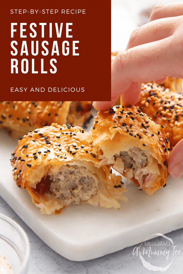 A festive sausage roll broken open on a white marble board. A hand reaches for it. Caption reads: Step-by-step recipe. Christmas sausage rolls. Easy and delicious.
