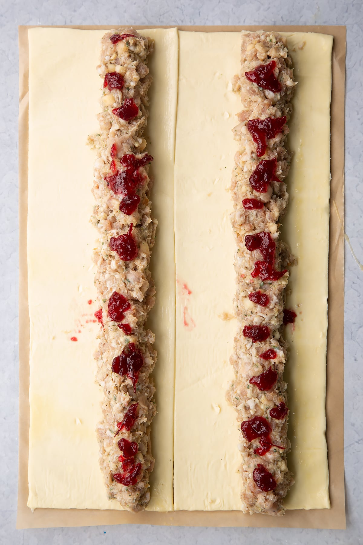 A sheet of puff pastry cut in half lengthways. Each half is egg washed and has a length of festive sausage meat down the middle, dotted with cranberry sauce.