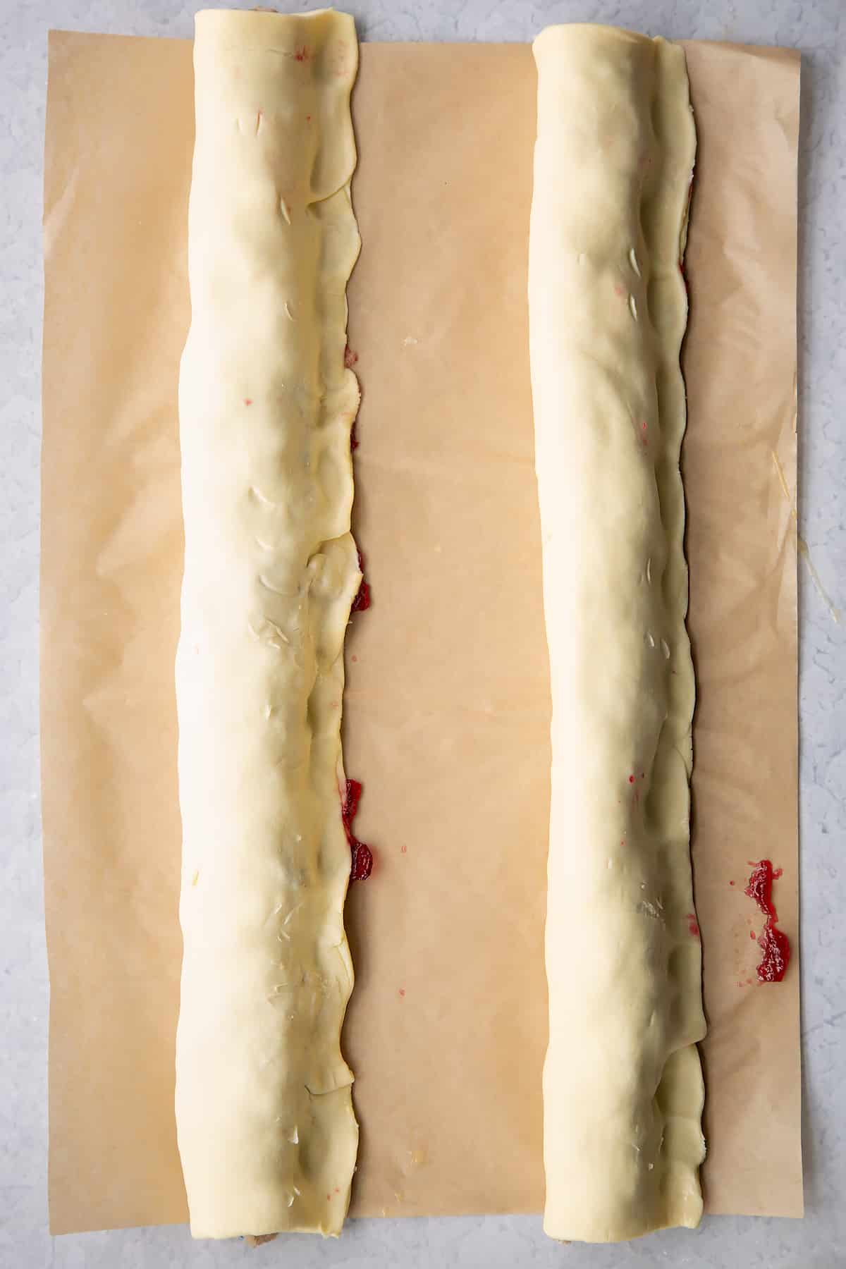 Two lengths of puff pastry wrapped around two lengths of festive sausage meat.