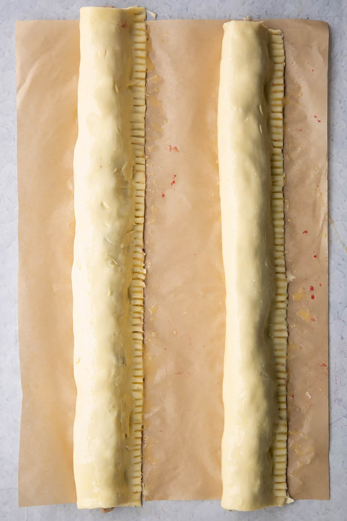 Two lengths of festive sausage meat wrapped in puff pastry. They are egg washed.