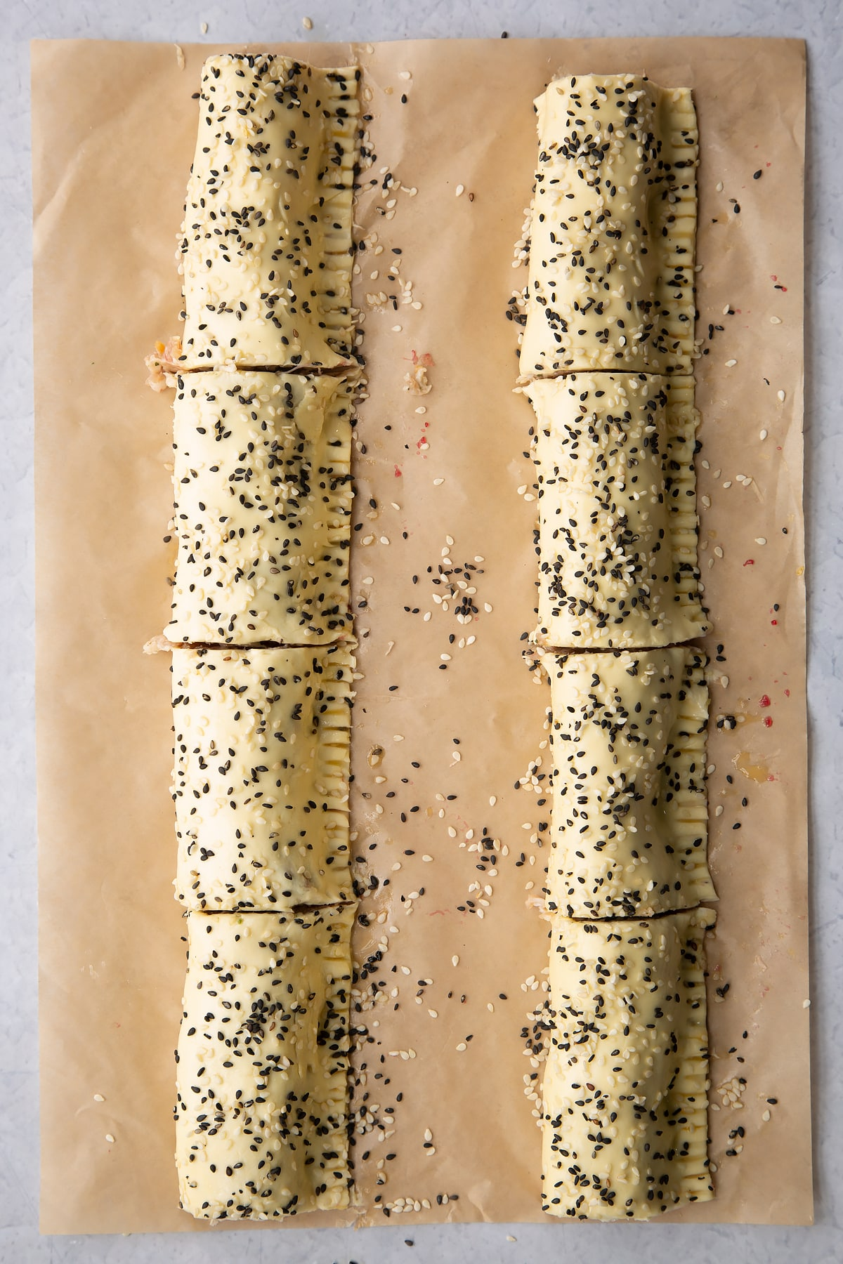 Two lengths of festive sausage meat wrapped in puff pastry , scattered with sesame seeds and cut into 8  in total.