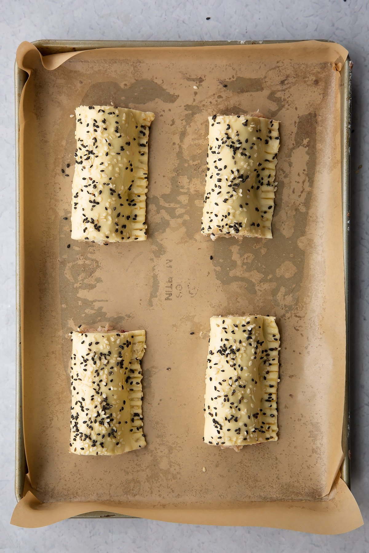 Four raw festive sausage rolls on a baking tray lined with baking paper.