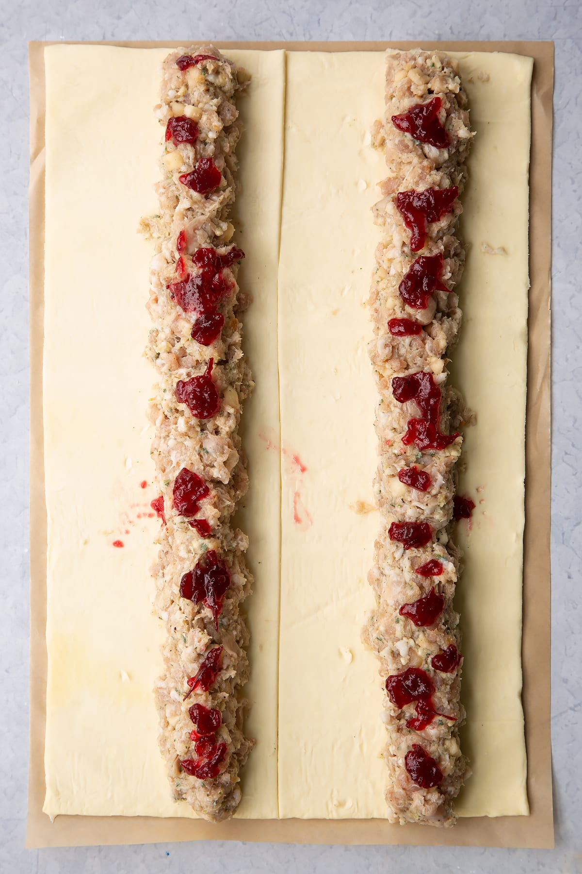 A sheet of puff pastry cut in half lengthways. Each half has a length of festive sausage meat down the middle, dotted with cranberry sauce.