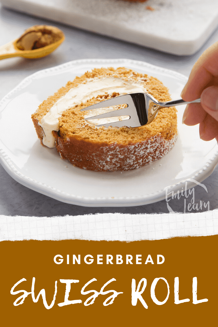 A slice of gingerbread Swiss roll on a white plate with a fork delving in. Caption reads: Gingerbread Swiss roll.