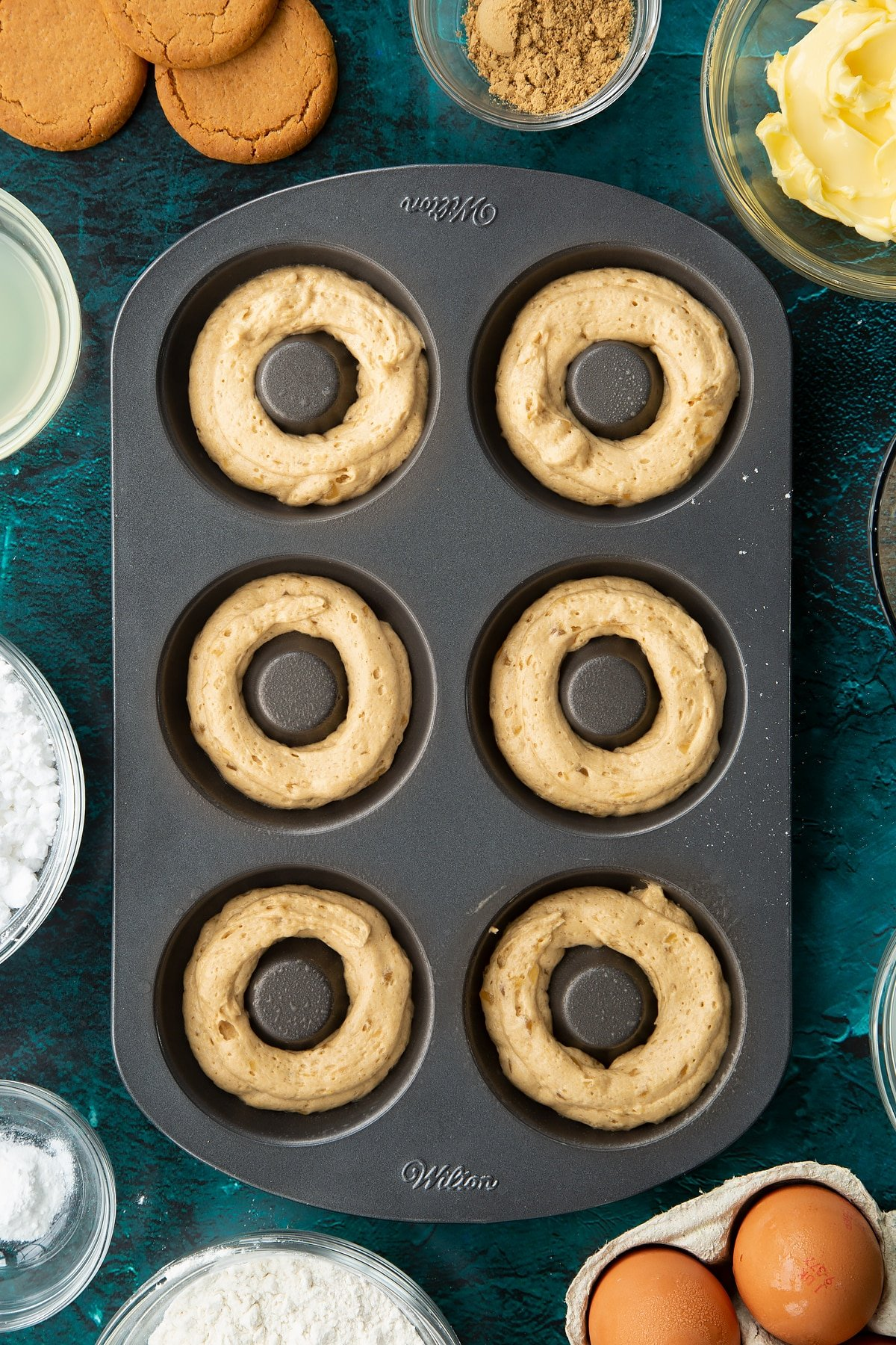 A metal donut pan with gingerbread donut batter piped into it.