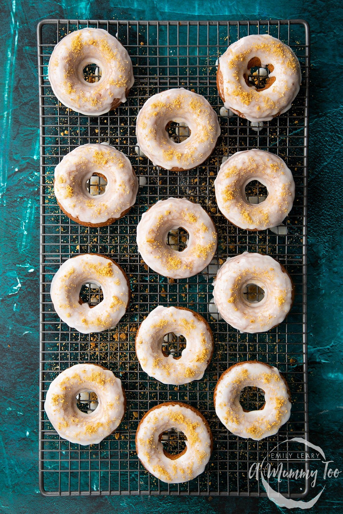 Freshly baked gingerbread donuts on a wire cooling rack. They have been dipped in lemon glaze and sprinkled with crushed gingernut biscuits.