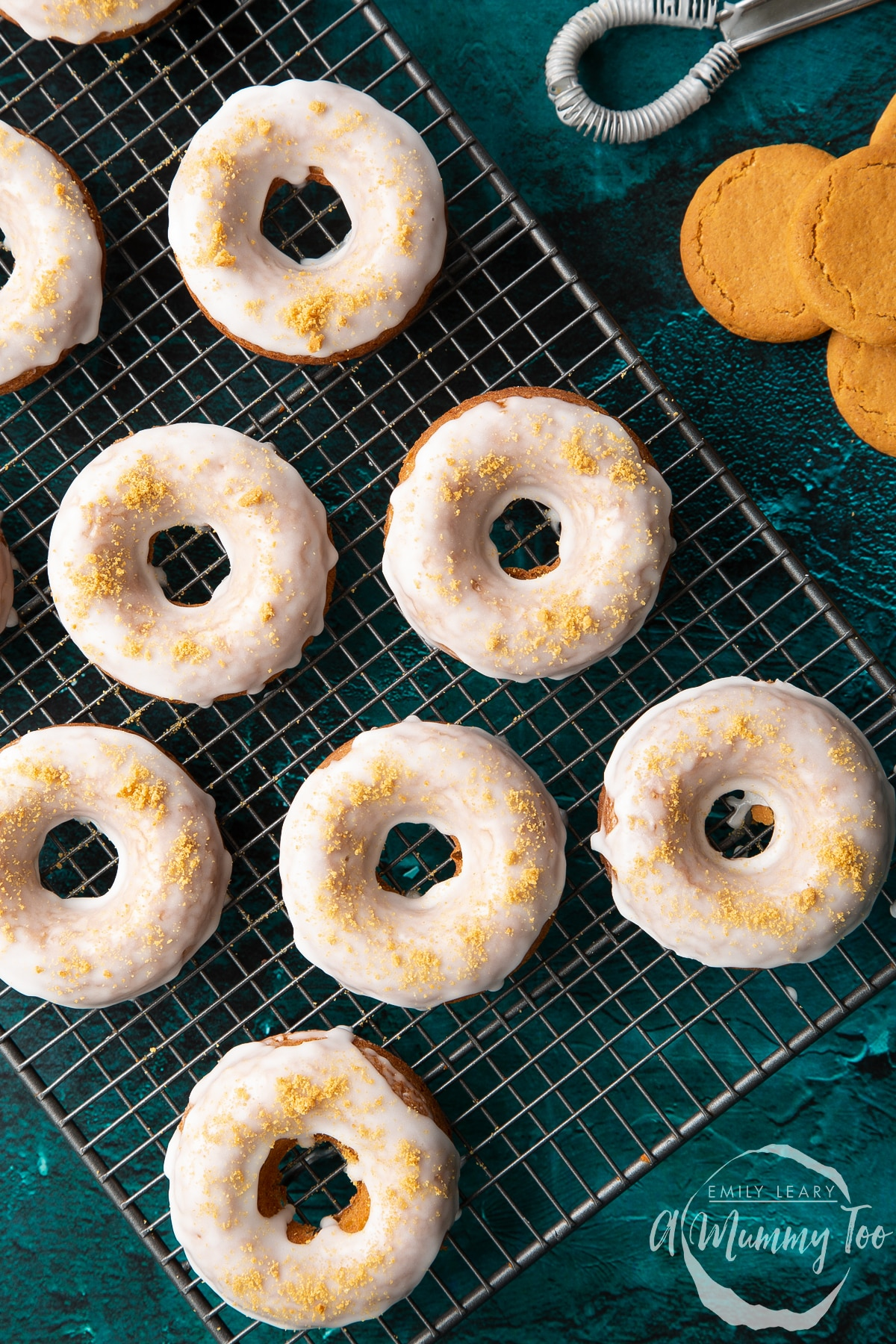 Baked gingerbread donuts with a lemon glaze on a wire cooling rack. Shown from above.