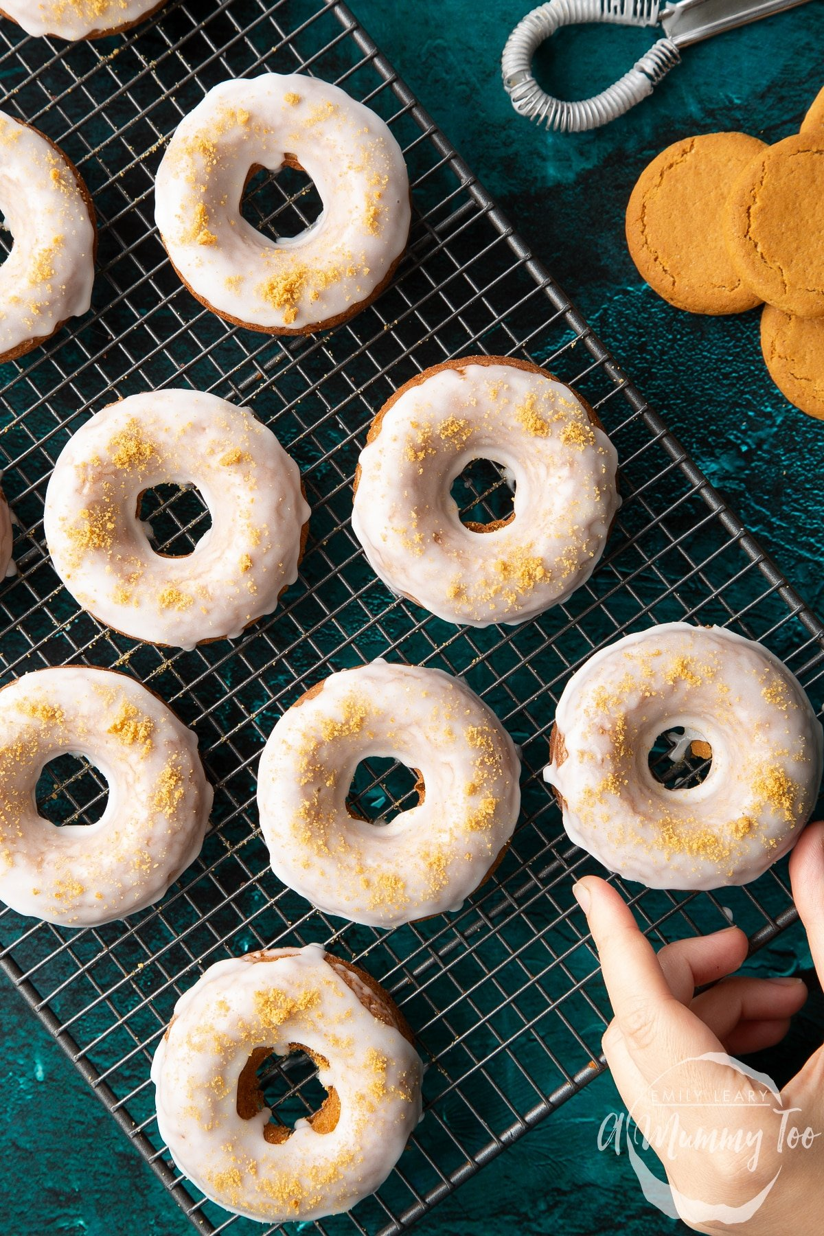 Baked gingerbread donuts with a lemon glaze on a wire cooling rack. A hand reaches for one. Shown from above.
