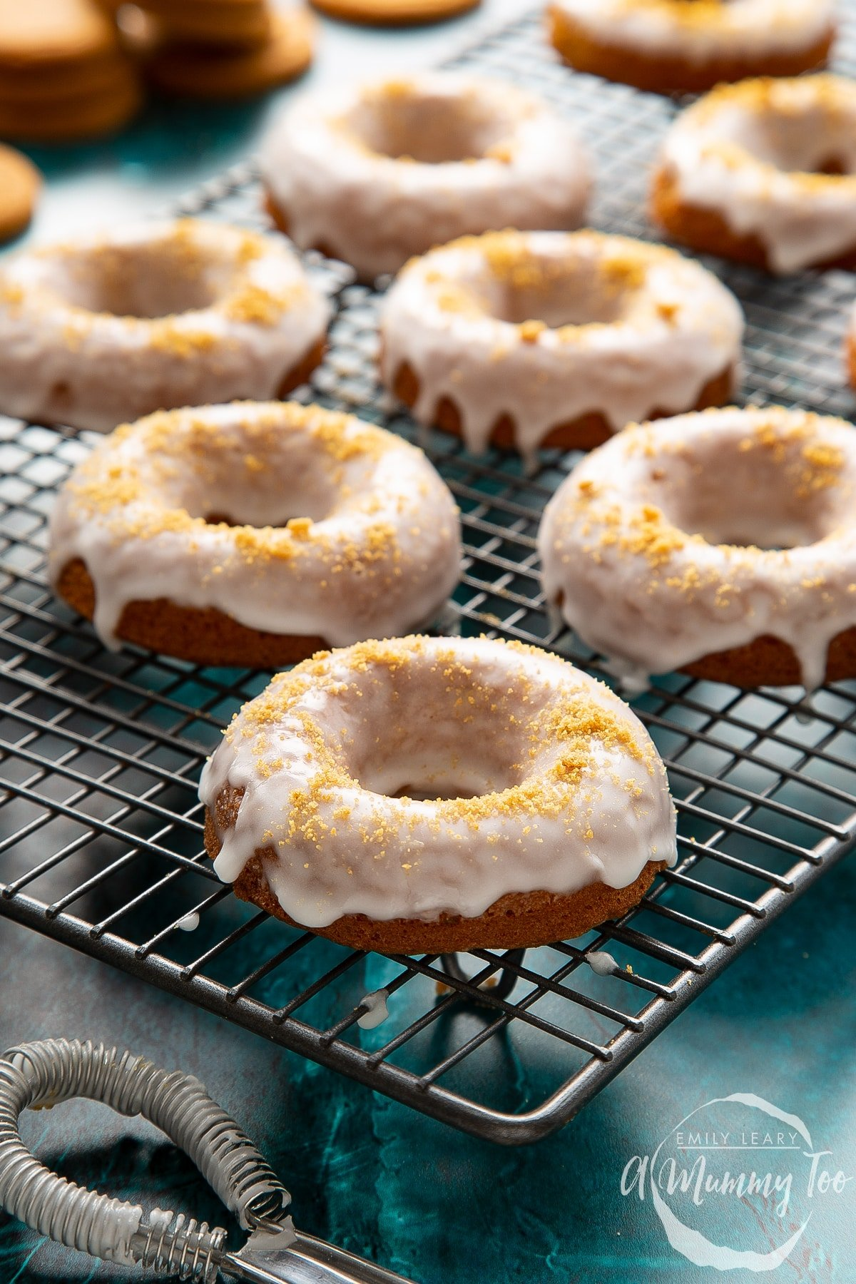 Baked gingerbread donuts with a lemon glaze on a wire cooling rack.