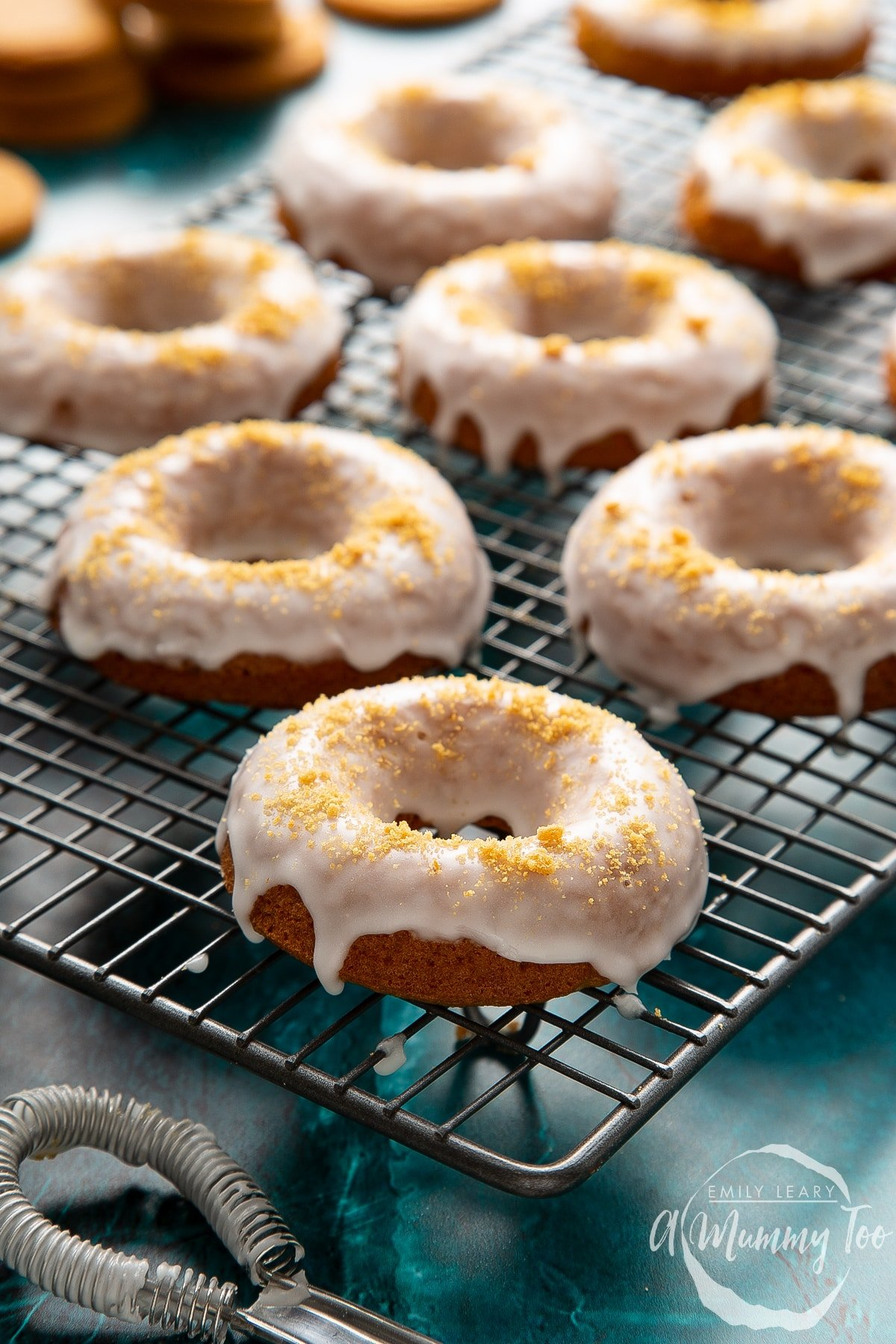 Baked gingerbread donuts, dipped in a lemon glaze on a wire cooling rack.