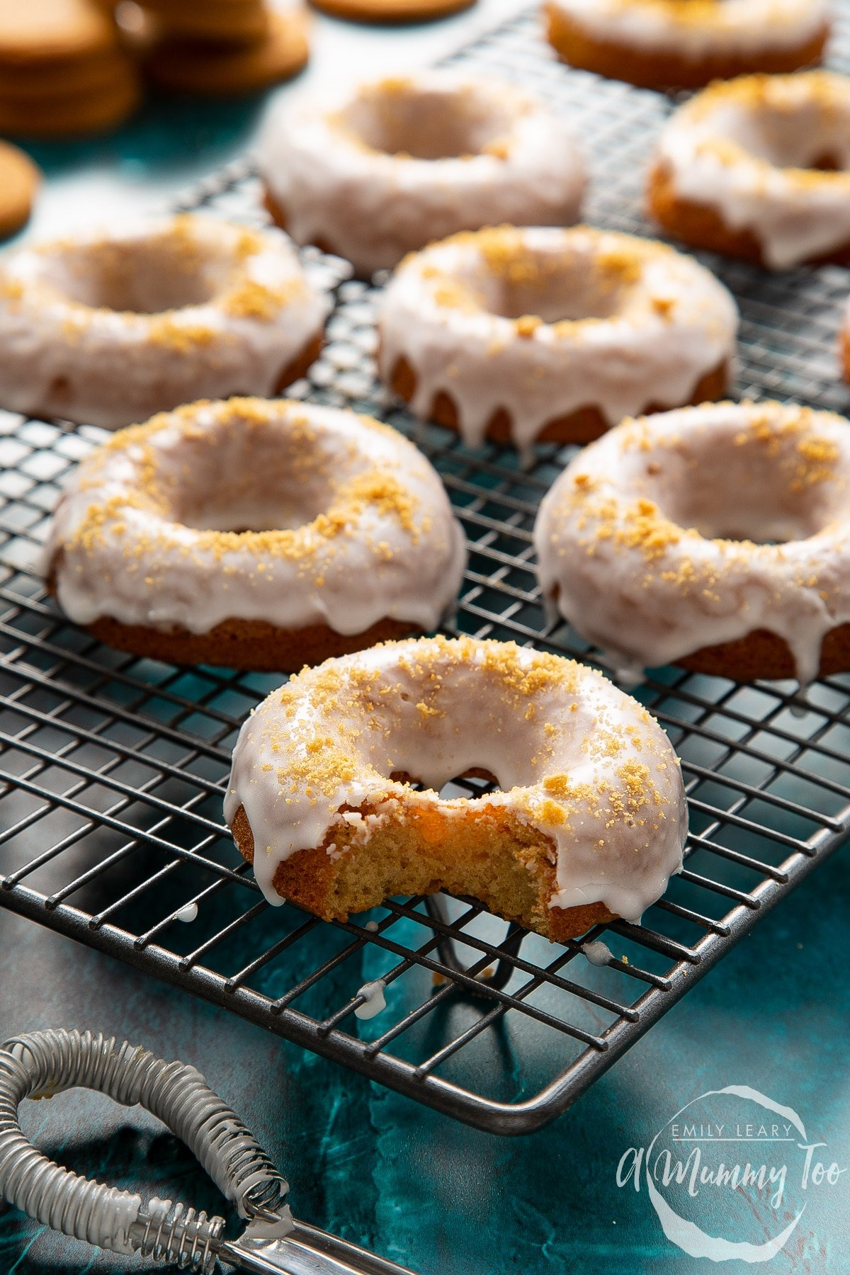Baked gingerbread donuts with a lemon glaze on a wire cooling rack. One has a bite out of it.