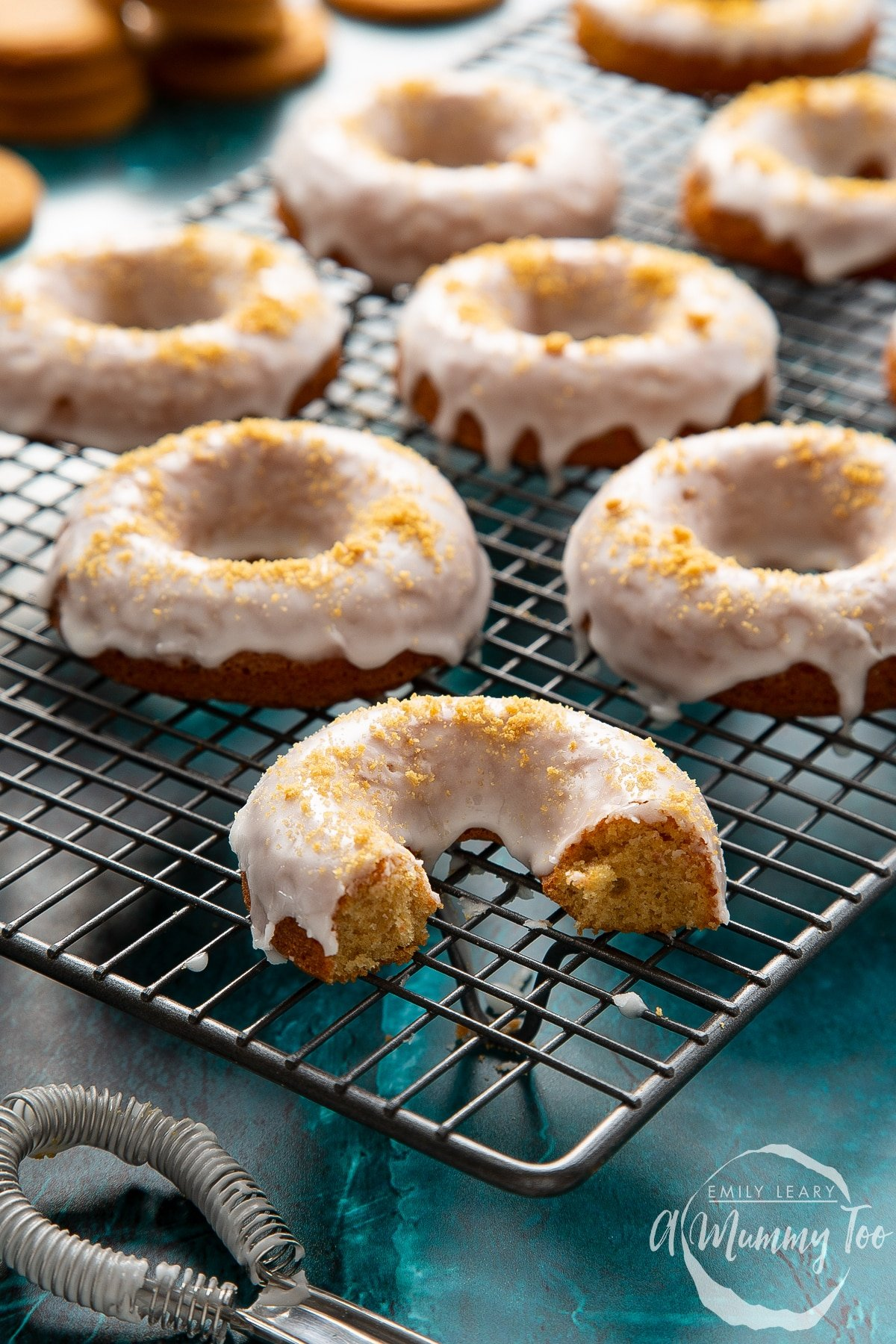 Baked gingerbread donuts with a lemon glaze on a wire cooling rack. One has been part eaten.
