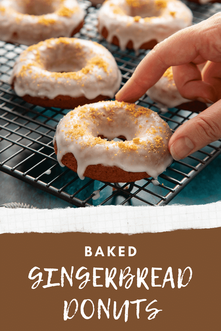Baked gingerbread donuts with a lemon glaze on a wire cooling rack. A hand reaches for one. Caption reads: Baked gingerbread donuts.