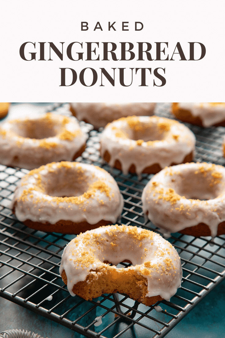 Baked gingerbread donuts with a lemon glaze on a wire cooling rack. One has a bite out of it. Caption reads: Baked gingerbread donuts.