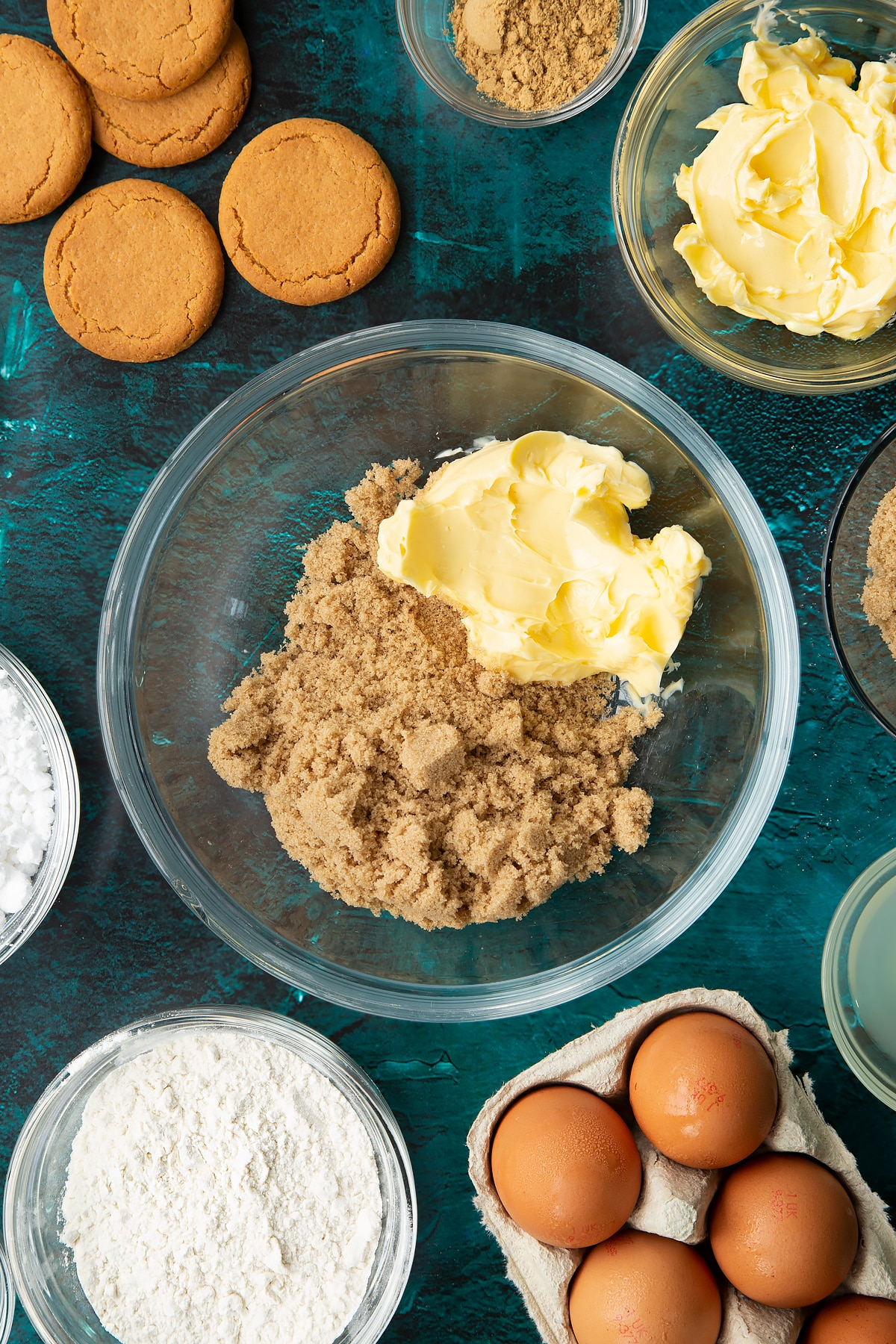 Butter and brown sugar in a glass mixing bowl. Ingredients to make gingerbread donuts surround the bowl.