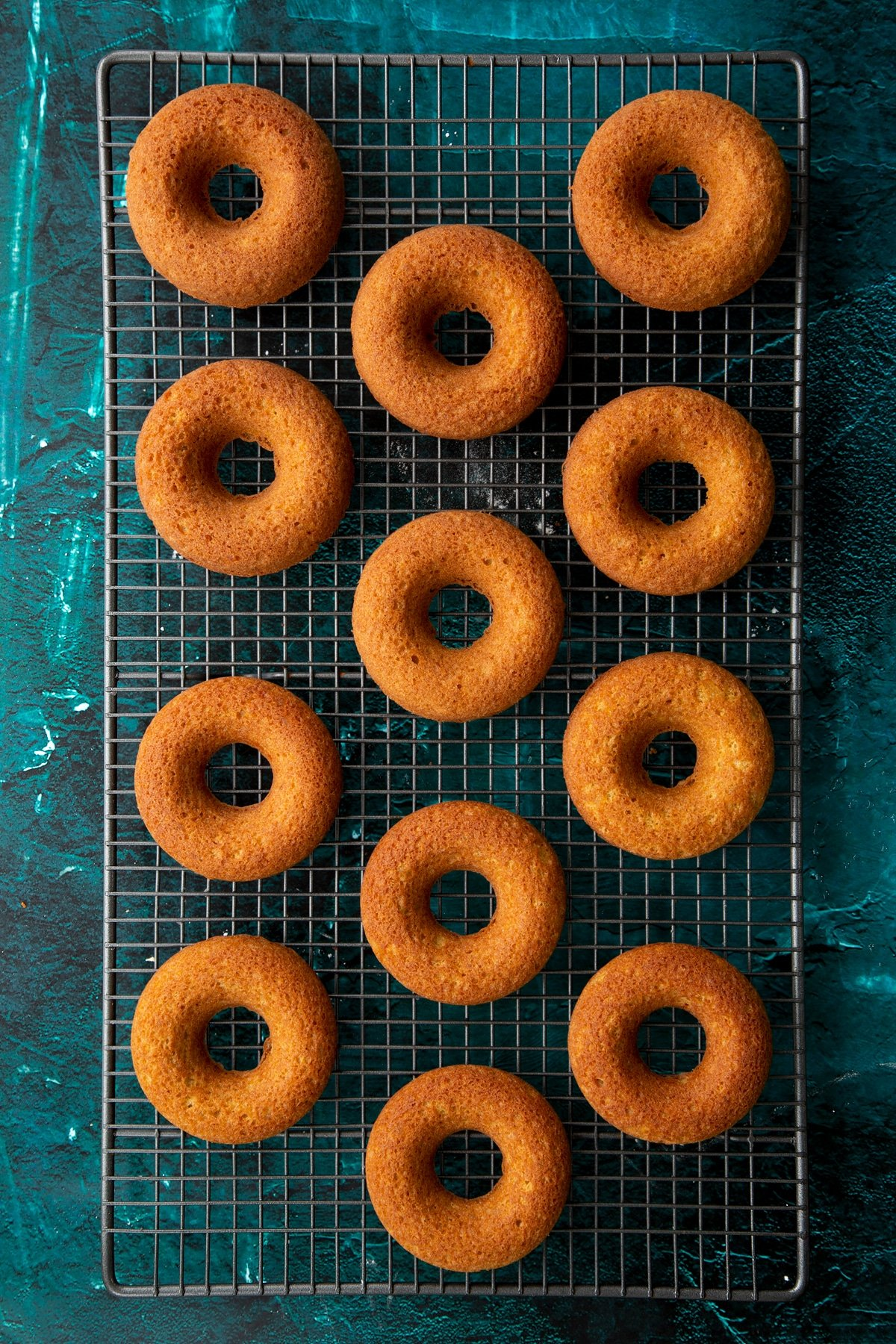 Freshly baked gingerbread donuts on a wire cooling rack.