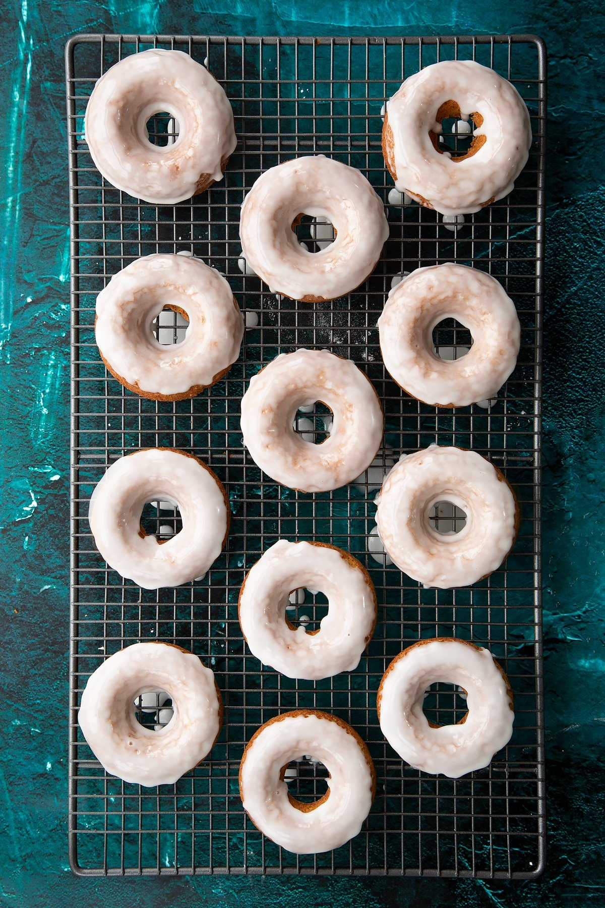 Freshly baked gingerbread donuts on a wire cooling rack. They have been dipped in lemon glaze.