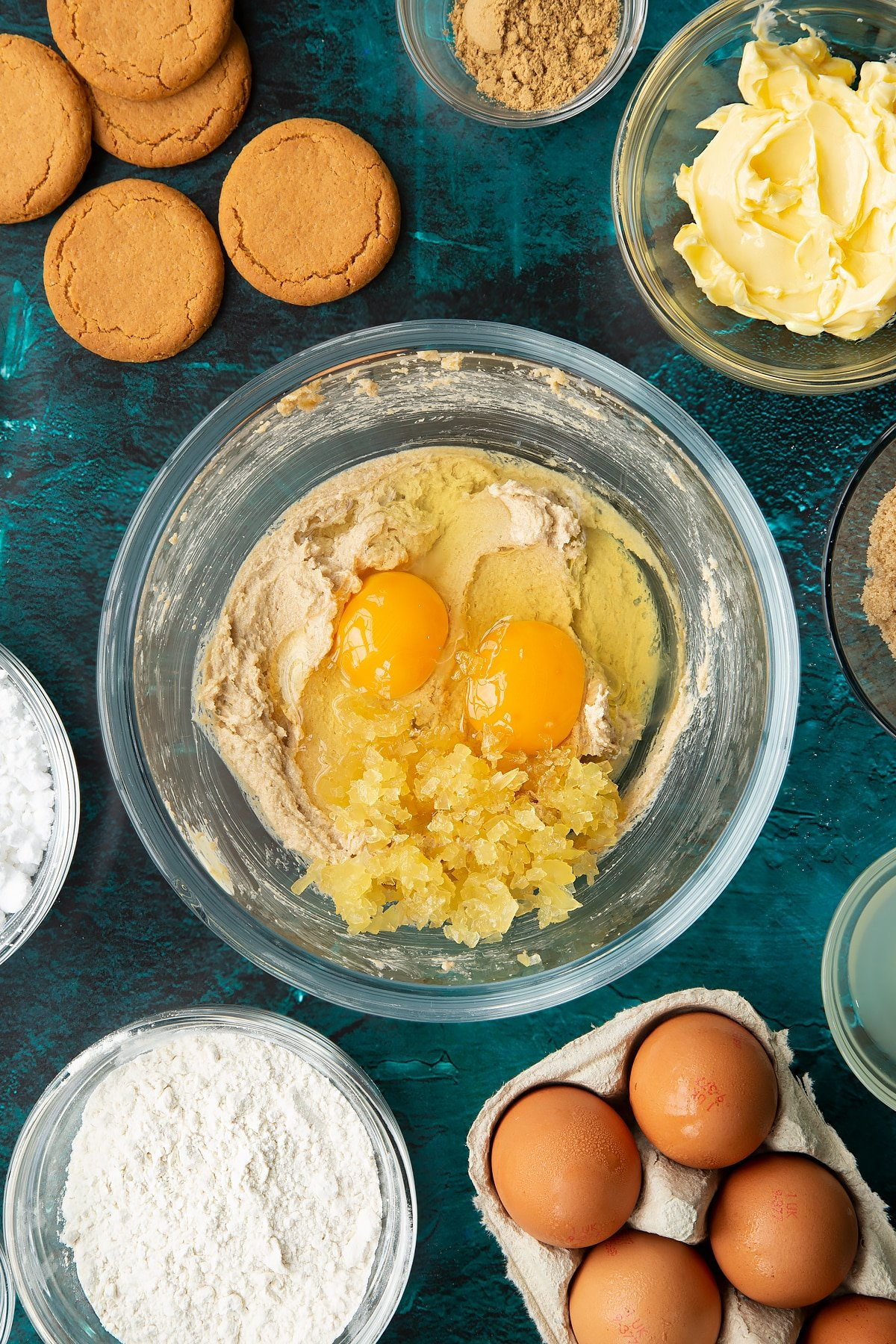 Butter and brown sugar beaten together in a glass mixing bowl with eggs, vanilla and chopped stem ginger on top. Ingredients to make gingerbread donuts surround the bowl.