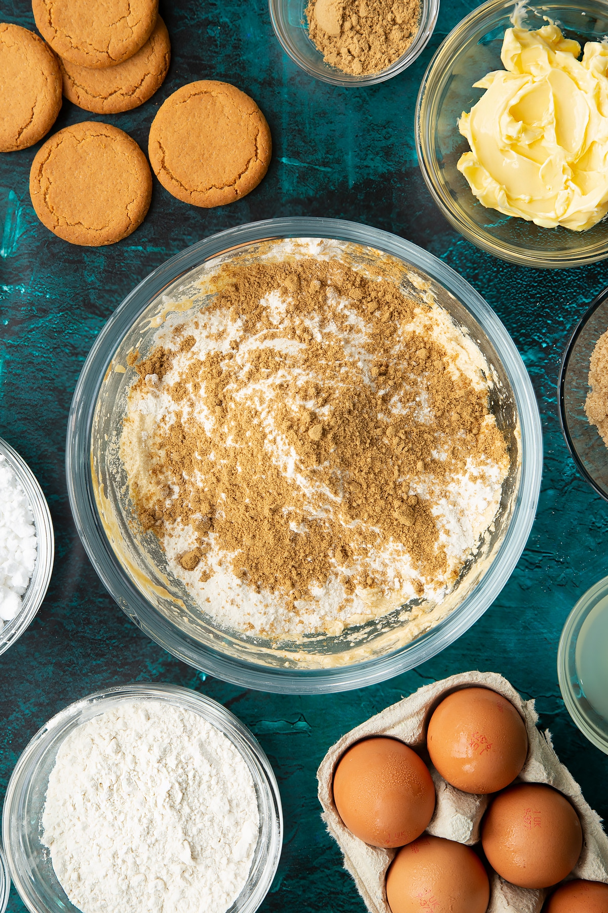 Butter, brown sugar, eggs, vanilla and chopped stem ginger beaten together in a glass mixing bowl with flour, baking powder and ginger on top. Ingredients to make gingerbread donuts surround the bowl.