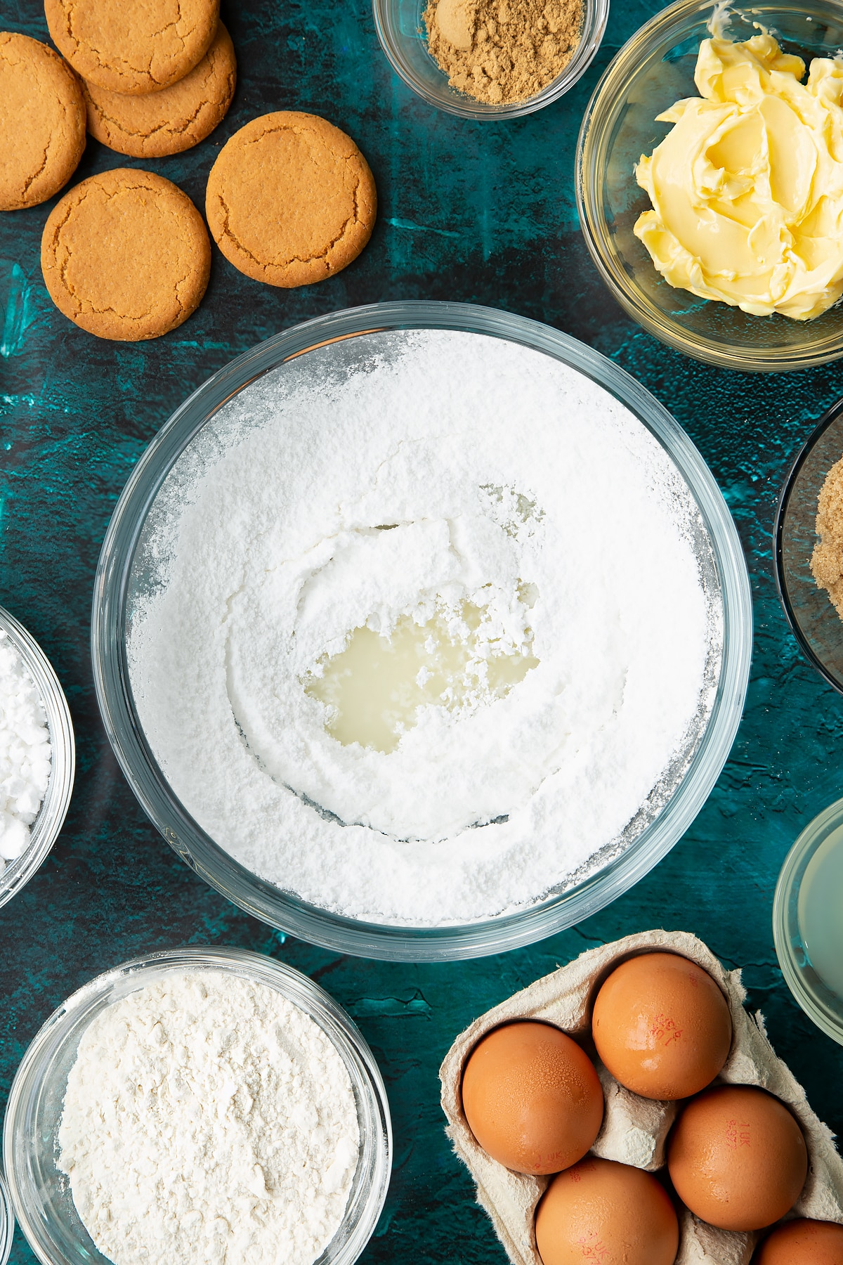Icing sugar and lemon juice in a glass mixing bowl. Ingredients to make gingerbread donuts surround the bowl.