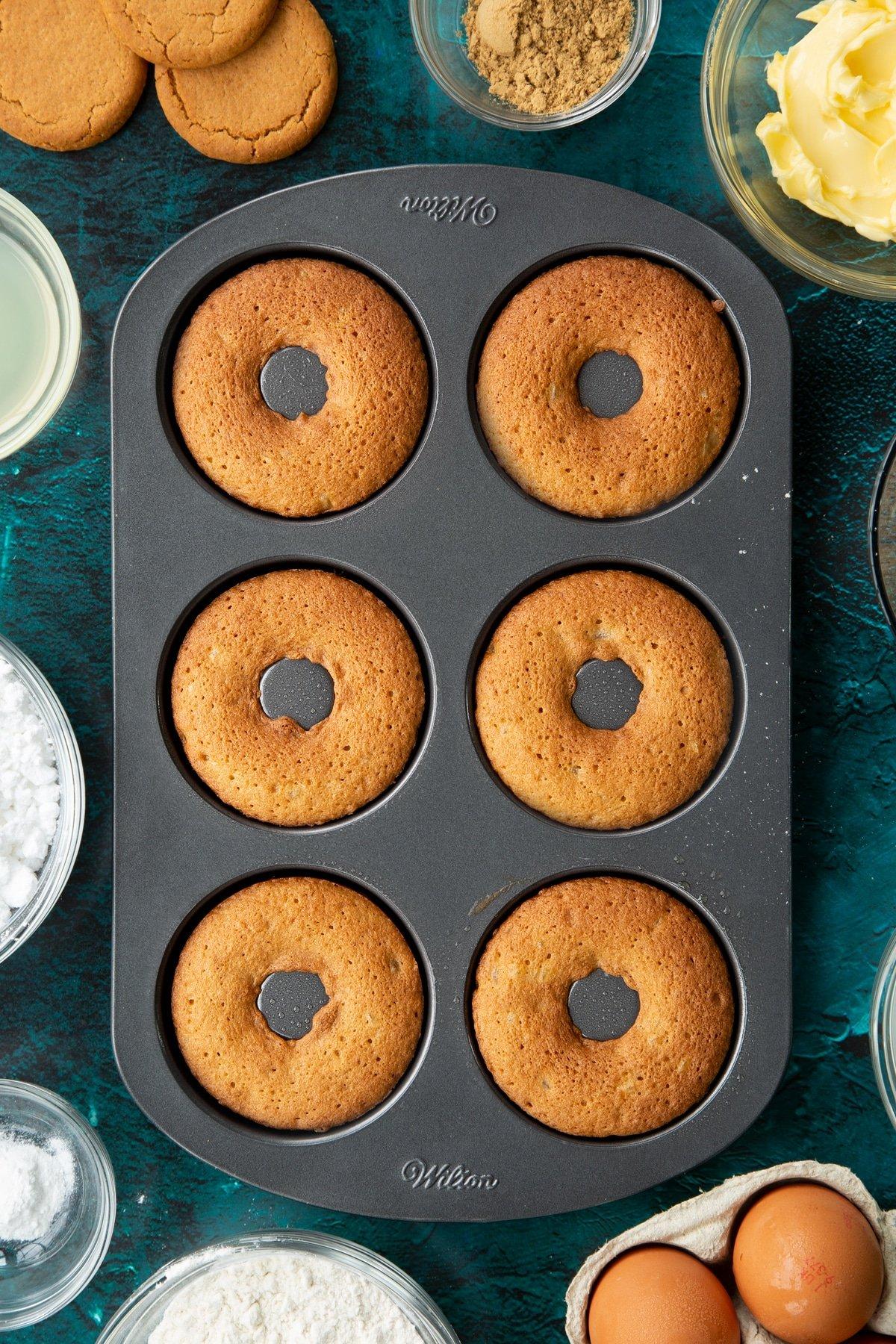 Freshly baked gingerbread donuts in a metal donut pan.