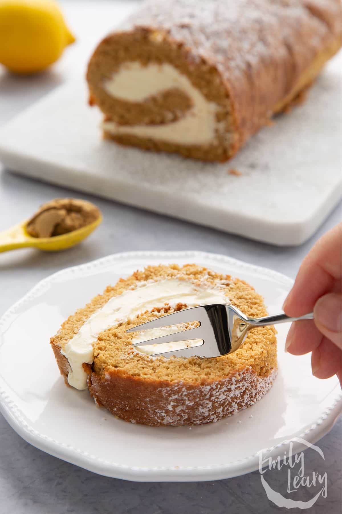 A slice of gingerbread Swiss roll on a white plate with a fork delving in.
