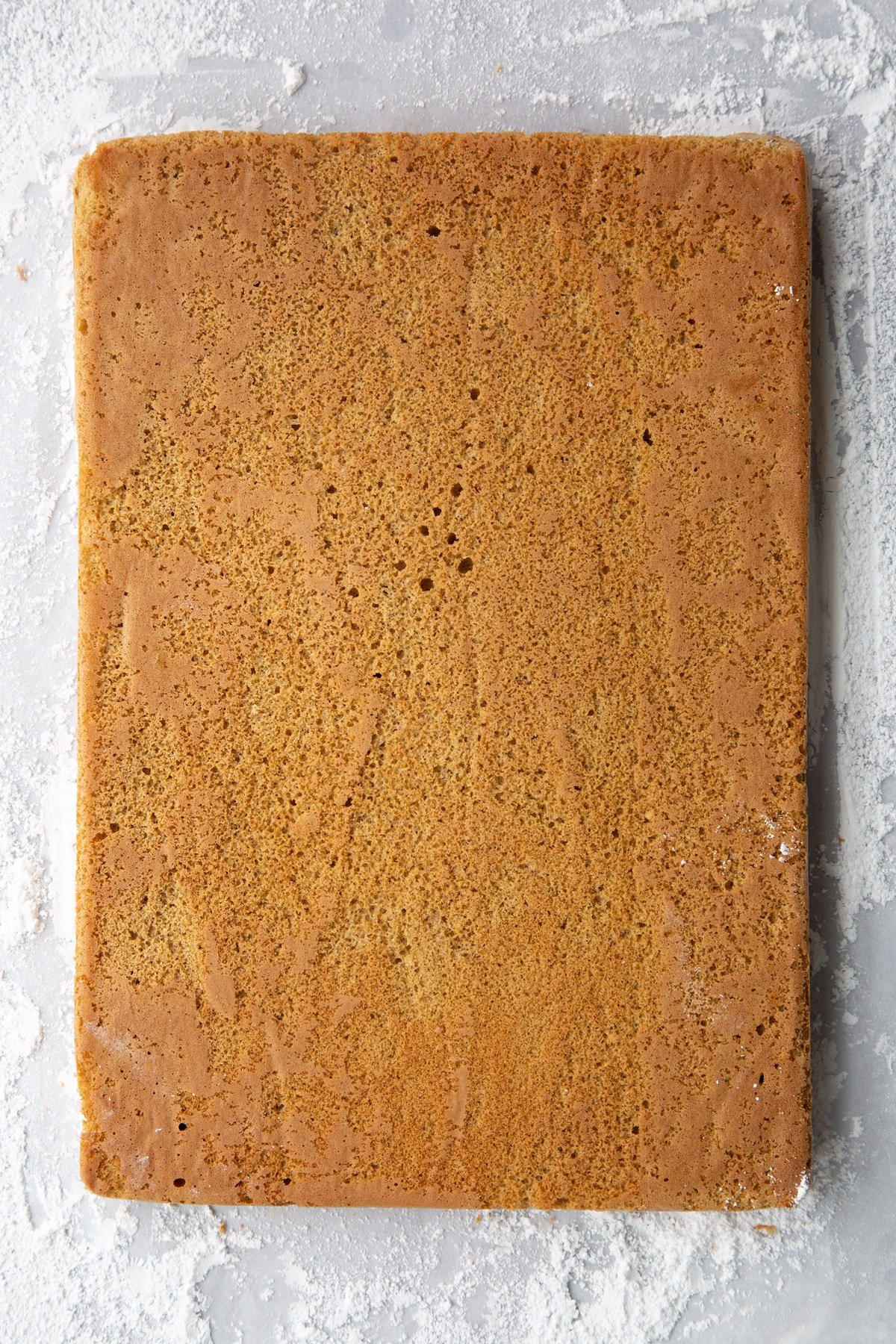 Baked gingerbread Swiss roll sponge, face down on a surface dusted with icing sugar. Backing paper removed.