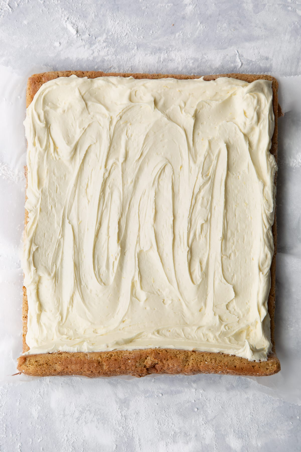 Gingerbread Swiss roll sponge unrolled and spread with lemon white chocolate buttercream.