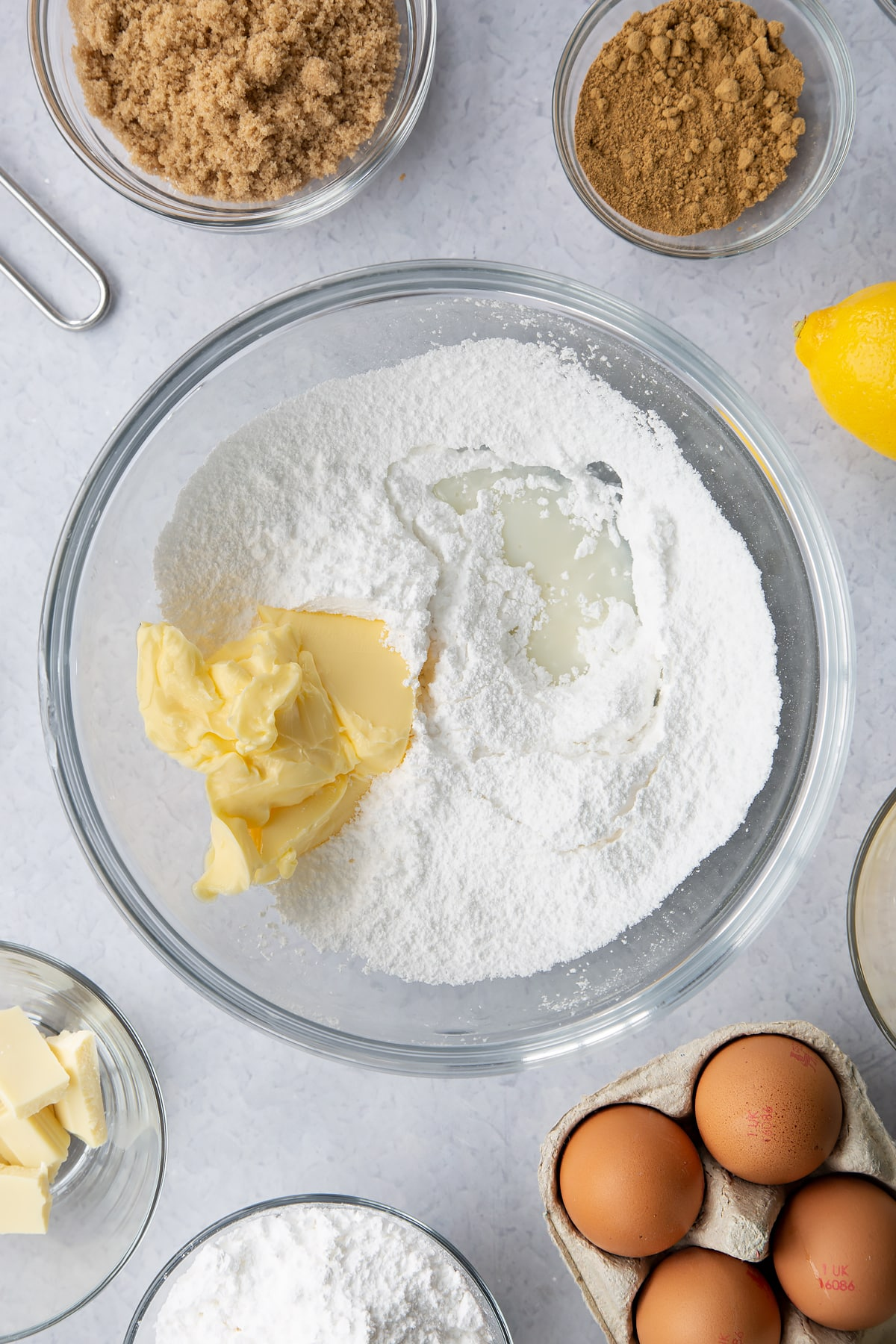 Icing sugar, butter and milk in a glass mixing bowl. Ingredients to make Gingerbread Swiss roll surround the bowl.