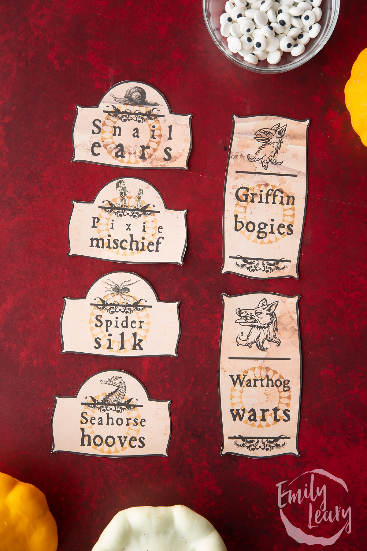 Cut out Halloween apothecary labels arranged on a red background.