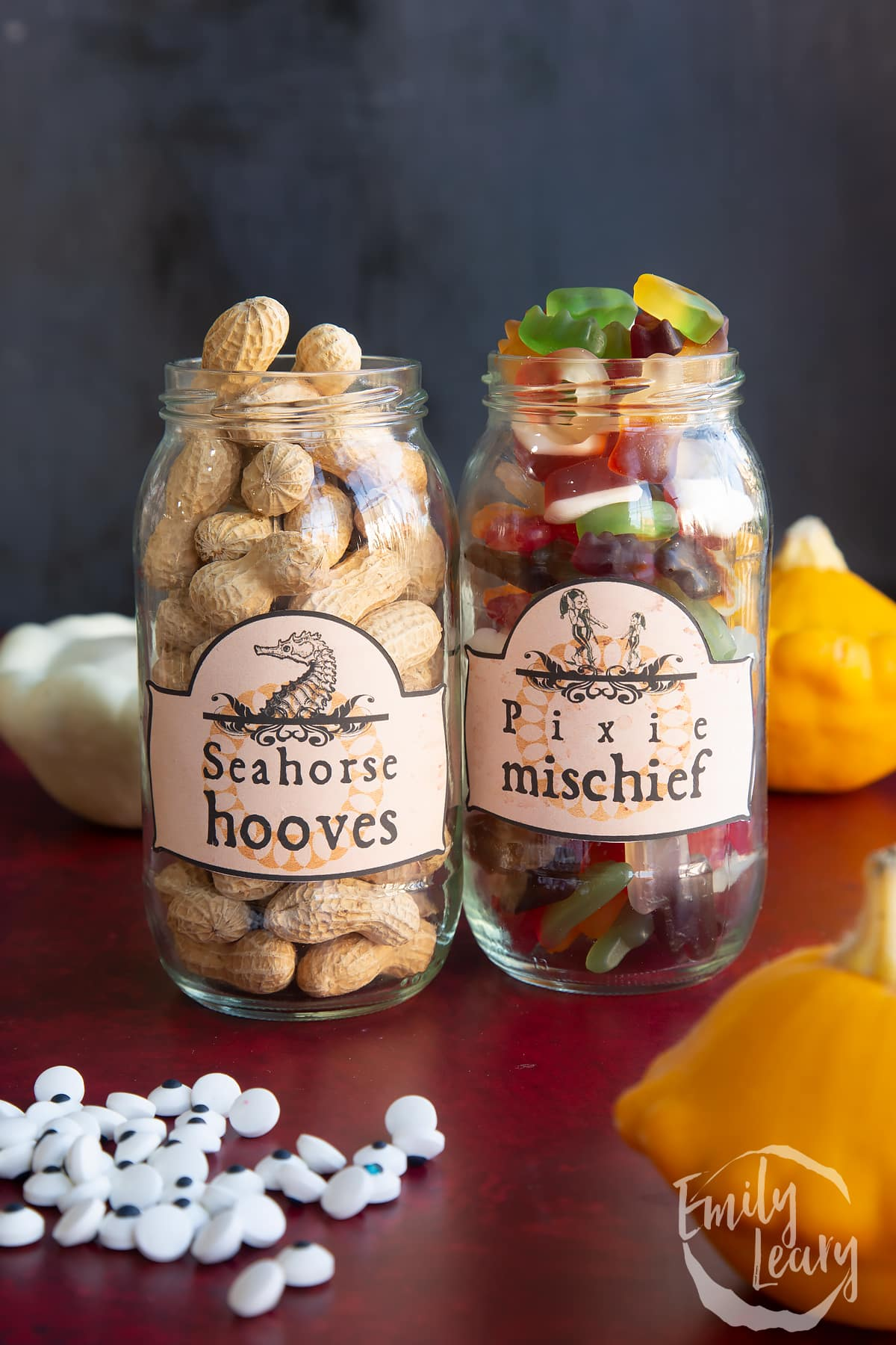 Two jars of different sizes, bearing Halloween apothecary labels. The jars contain Monkey Nuts (Seahorse hooves) and mini gummy sweets (Pixie mischief)