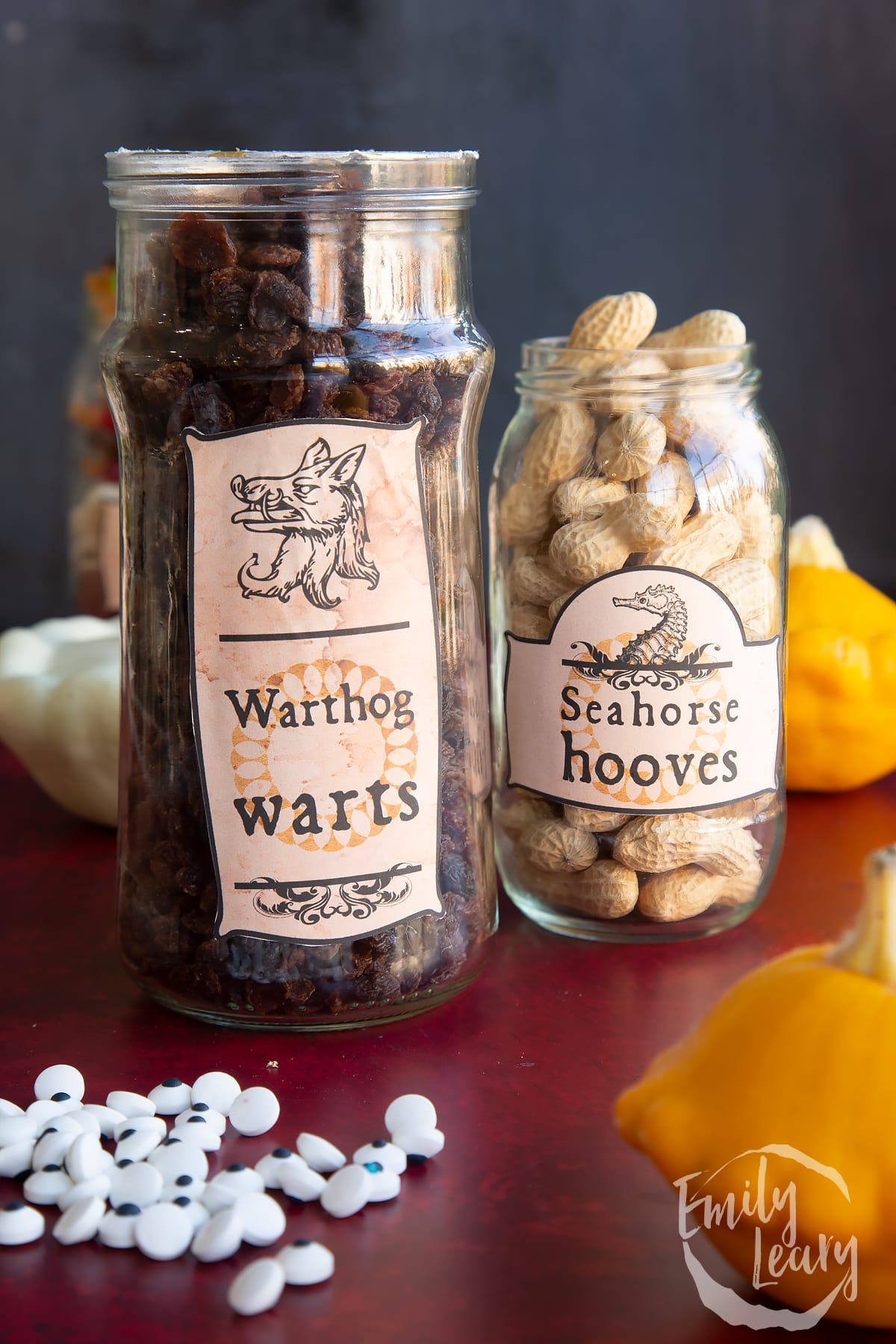 Two jars of different sizes, bearing Halloween apothecary labels. The jars contain raisins (Warthog warts) and Monkey Nuts (Seahorse hooves).