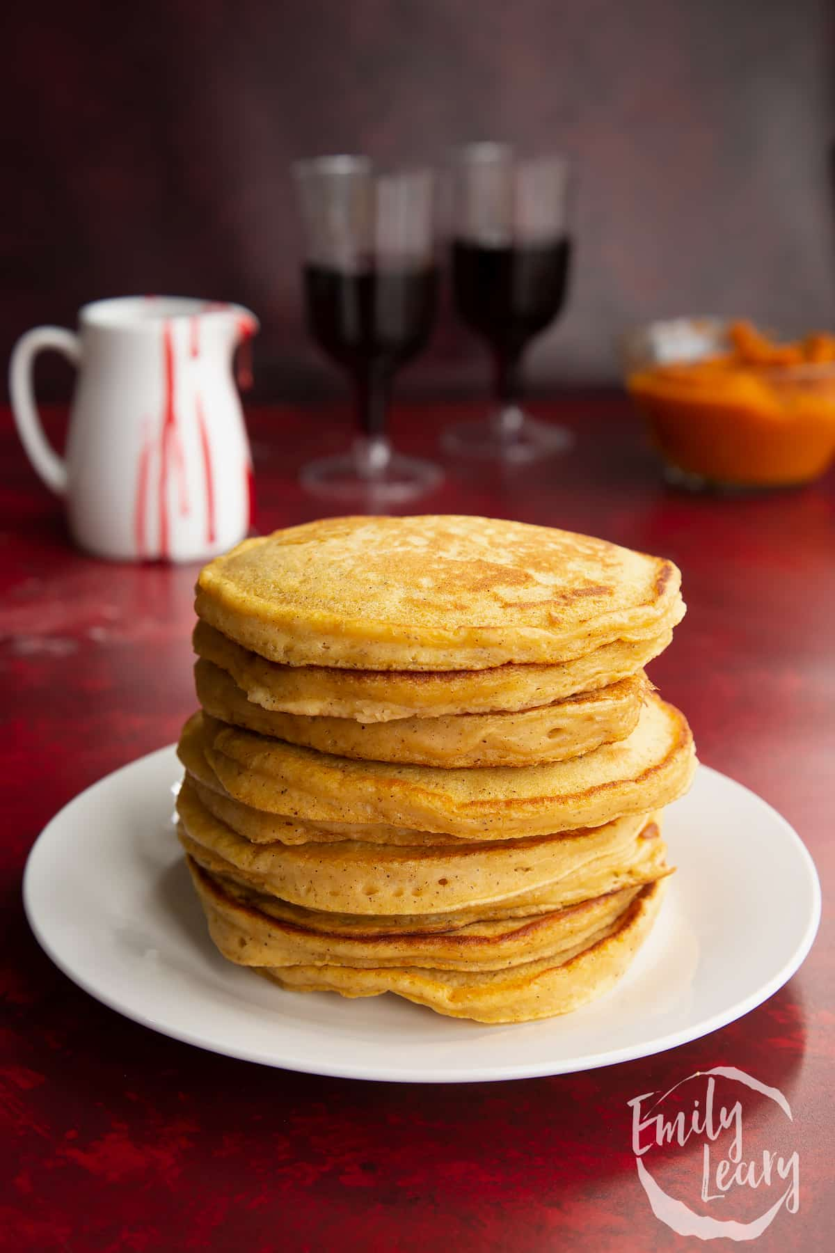 Halloween pumpkin pancakes stacked on a white plate.