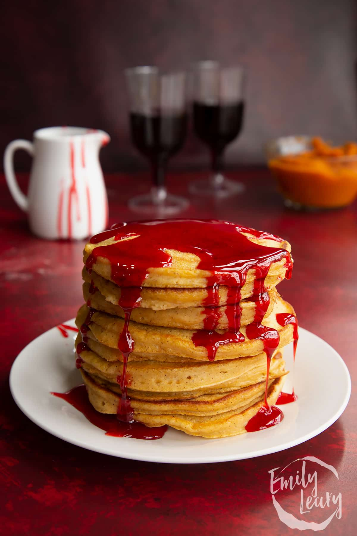 Halloween pancakes stacked on a white plate, drizzled with red syrup.