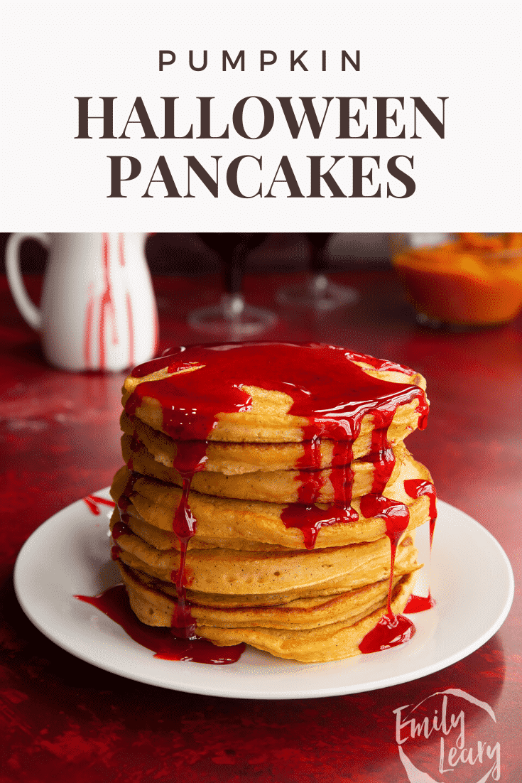 Halloween pancakes stacked on a white plate, drizzled with red syrup. Caption reads: Pumpkin Halloween pancakes.
