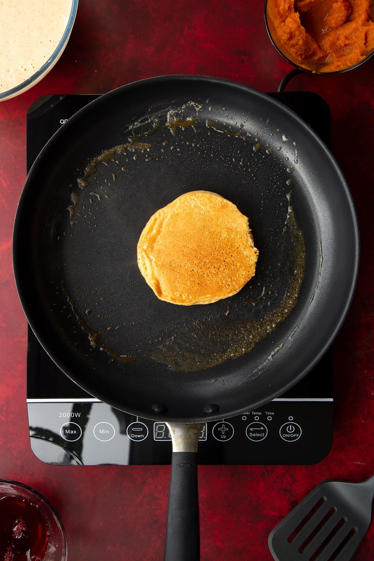 A cooked pumpkin pancake in a greased frying pan. Ingredients to make Halloween pancakes surround the pan.
