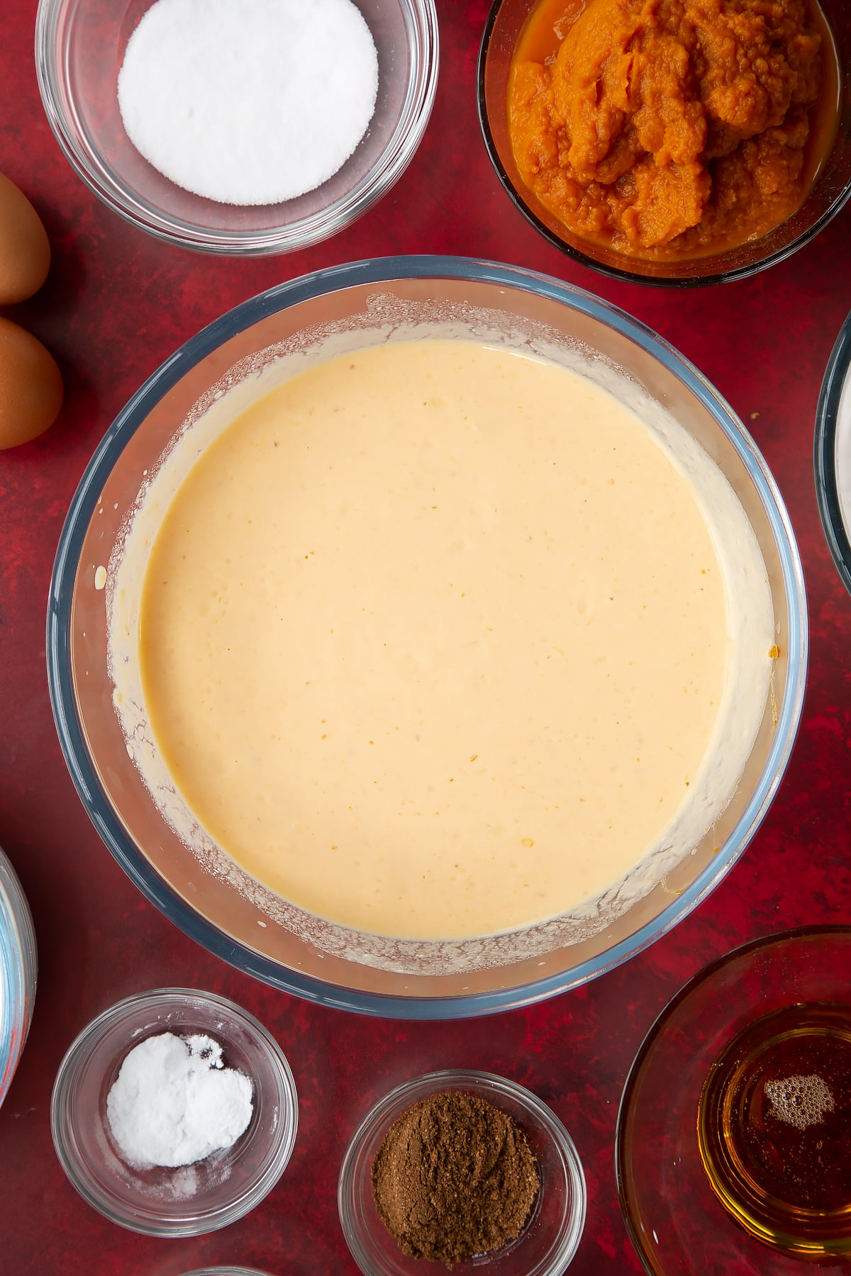 Yogurt, egg, milk and pumpkin puree, whisked together in a glass mixing bowl. Ingredients to make Halloween pancakes surround the bowl.