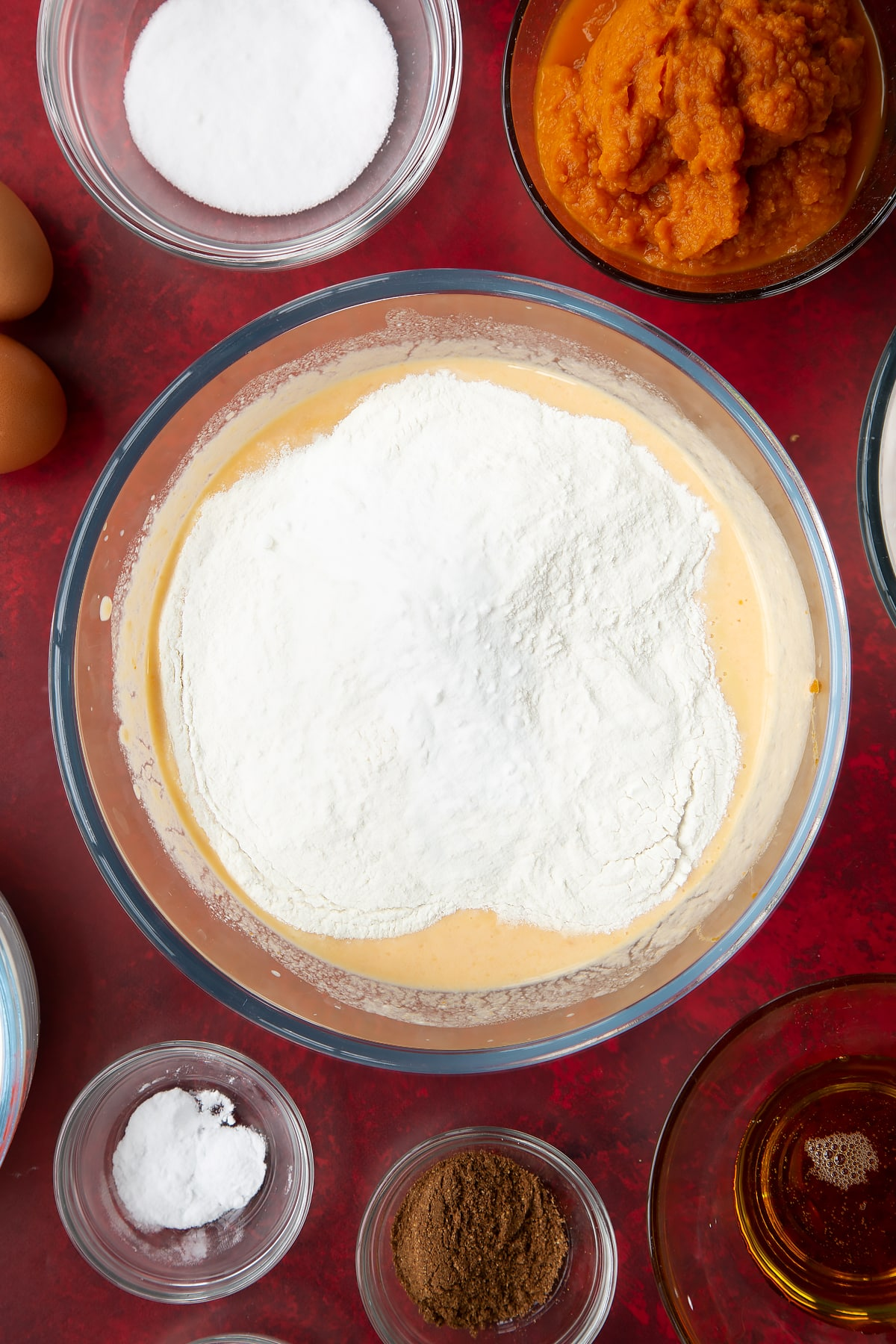 Whisked yogurt, egg, milk and pumpkin puree with flour, sugar, baking powder, bicarbonate of soda and mixed spice in a glass mixing bowl. Ingredients to make Halloween pancakes surround the bowl.