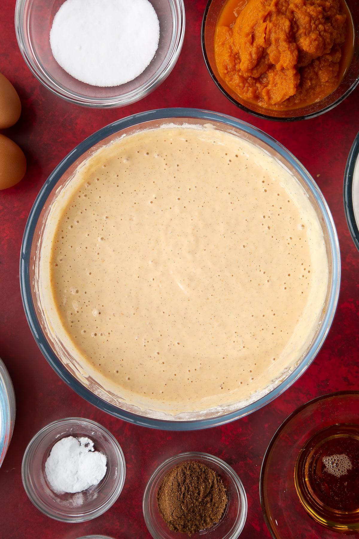 Pumpkin pancake batter in a glass mixing bowl. Ingredients to make Halloween pancakes surround the bowl.