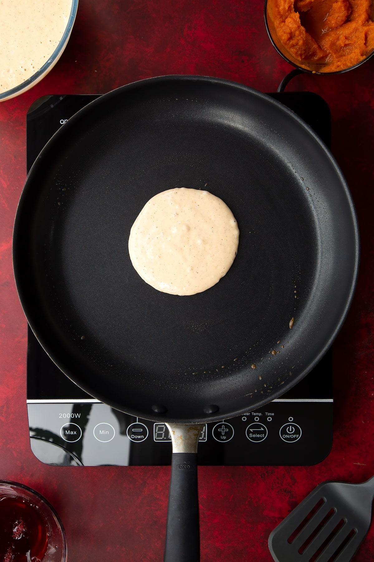Pumpkin pancake batter in a greased frying pan. Ingredients to make Halloween pancakes surround the pan.