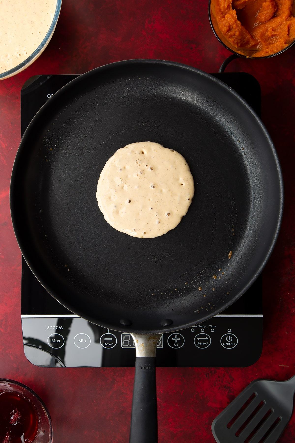 Pumpkin pancake batter bubbling in a greased frying pan. Ingredients to make Halloween pancakes surround the pan.