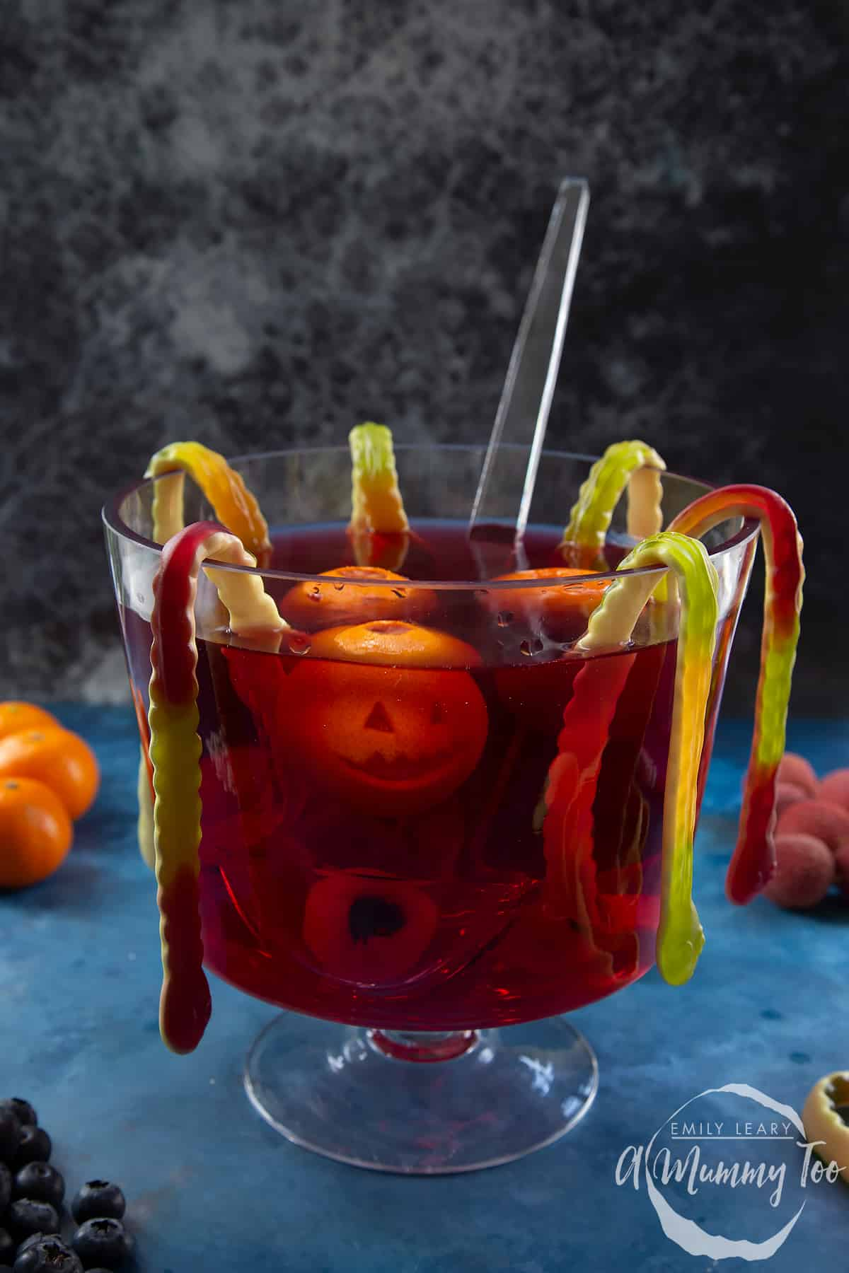 Halloween punch in a glass punch bowl. It is a red liquid, decorated with gummy snakes, jack'o'lantern clementines and lychee and blueberry eyeballs.