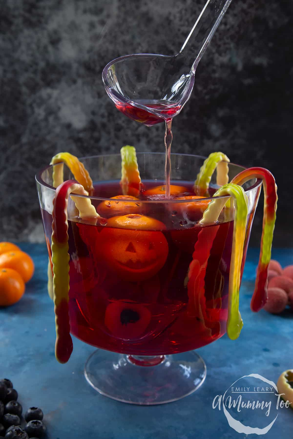 Halloween punch in a glass punch bowl. It is a red liquid, decorated with gummy snakes, jack'o'lantern clementines and lychee and blueberry eyeballs. A ladle drizzles punch into the bowl.