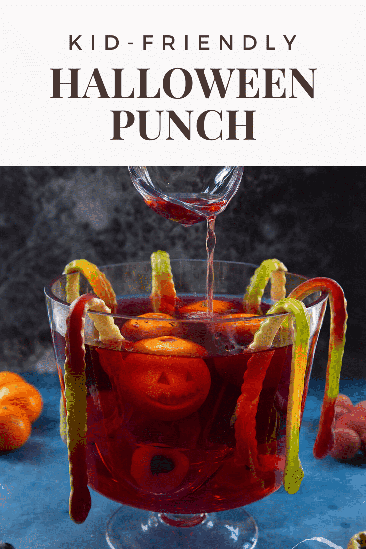 Halloween punch, decorated with fruit and gummy snakes. Some punch is being ladled from the bowl. Caption reads: Kid friendly Halloween punch.