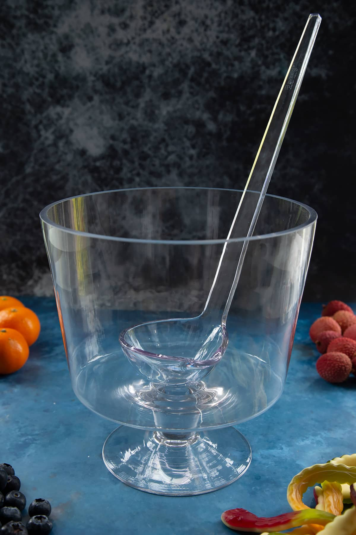 A glass punch bowl with ladle. Ingredients to make Halloween punch surround the bowl.