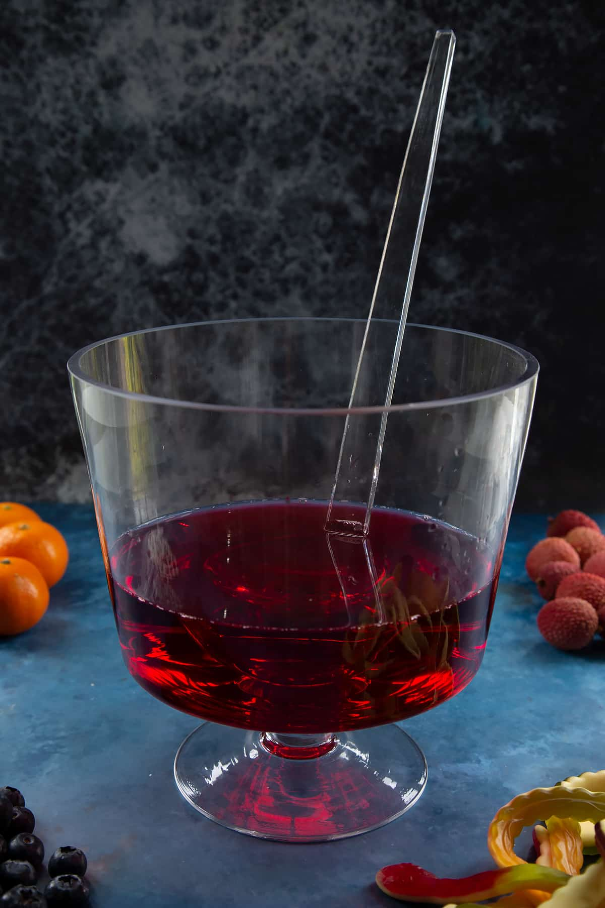 A glass punch bowl with ladle. It's part filled with cranberry juice. Ingredients to make Halloween punch surround the bowl.
