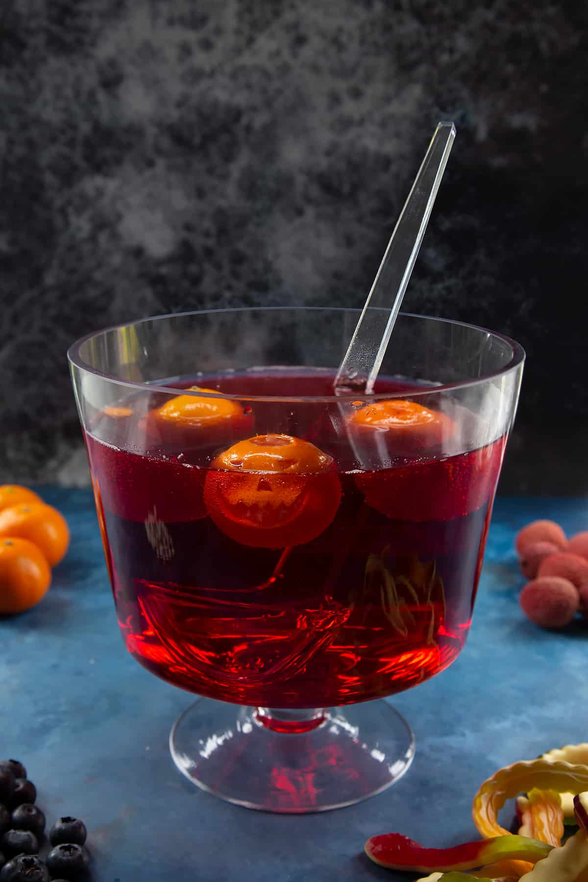 A glass punch bowl with ladle. It's filled with cranberry juice and lemonade. Jack'o'lantern clementines float in the liquid. Ingredients to make Halloween punch surround the bowl.