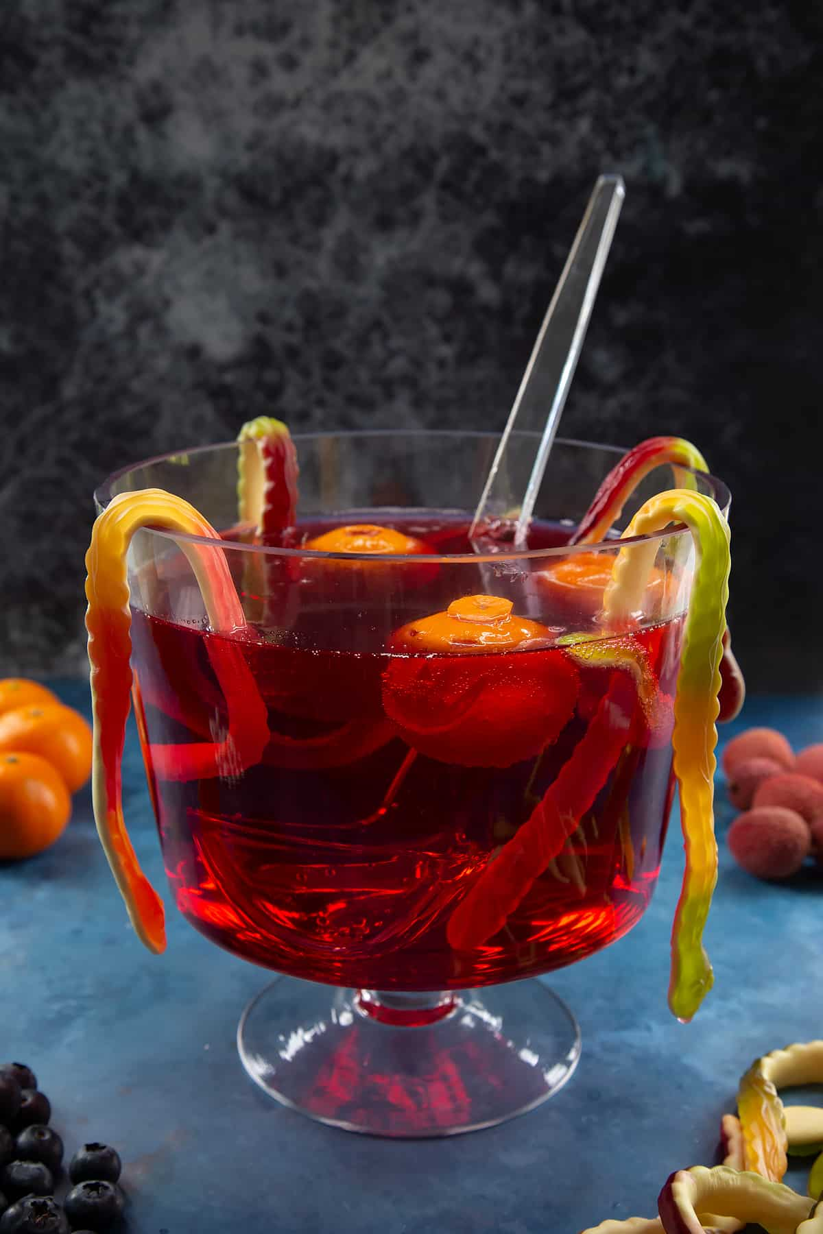 A glass punch bowl with ladle. It's filled with cranberry juice and lemonade. Jack'o'lantern clementines float in the liquid and gummy snakes hang around the bowl. Ingredients to make Halloween punch surround the bowl.