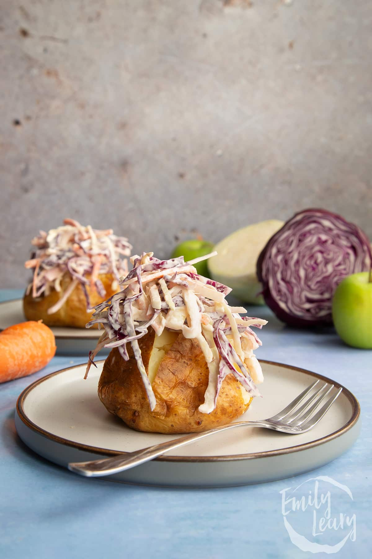 Jacket potato with homemade coleslaw on a plate with a fork.
